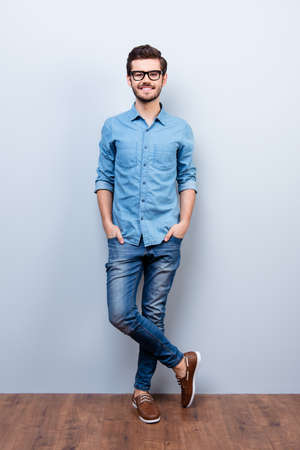 he: Full size vertical portrait of cheerful brunet young man in casual stylish wear. He looks at camera on lifgt background