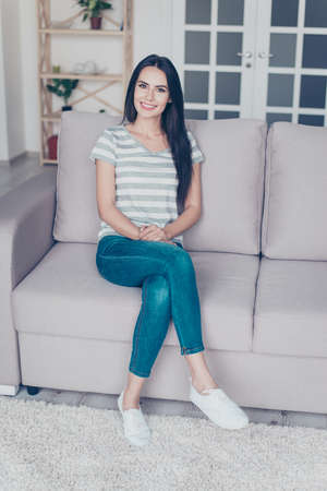 Vertical portrait of cute pretty smiling woman sitting with crossed legs on a sofa at home