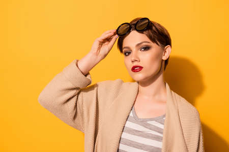 Stylish look of the model in fashionable sunglasses and casual clothes on the bright yellow background. She is serious and looks straight, holding the glasses Stock Photo