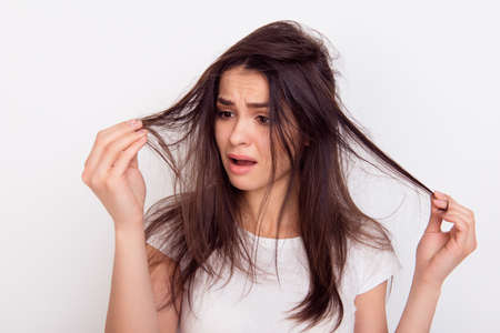 Close up portrait of frustrated young brunette woman with messed hair on white background