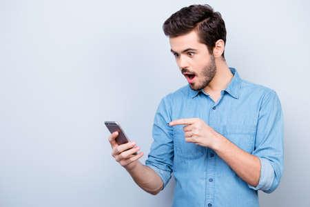 Joven sorprendido sostiene el teléfono y lee el mensaje señalando con el dedo
