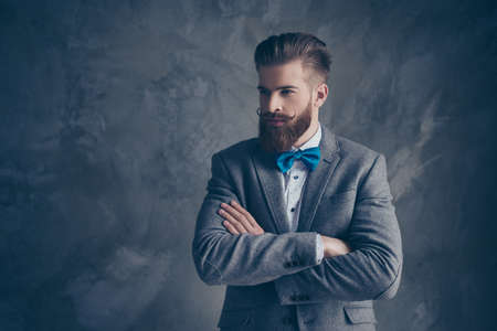 Confident stylish man in suit and bow with beard crossing his hands