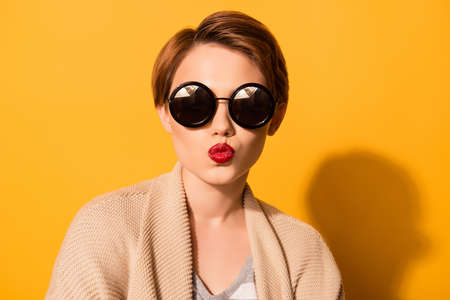 Fashionable young cute girl in trendy sunglasses sends a kiss  against bright yellow background