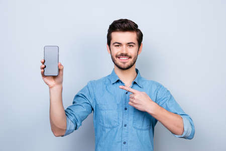 Portrait of happy young man pointing with his finger on the screen of his smartphone on light blue background Stock Photo