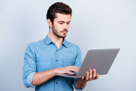 Portrait of concentrated young serious man typing on his laptop on light blue background Stock Photo