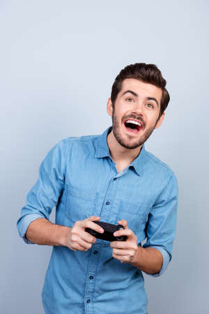 Portrait of young man holding joystick and playing videogames. He is very excited