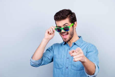 Cool! Playful handsome young man in bright green glasses is pointing on camera with open mouth