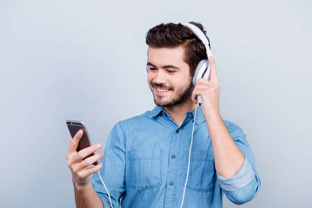 Excited young handsome man is listening to music on his pda with big white earphones, he looks at the screen of the phone