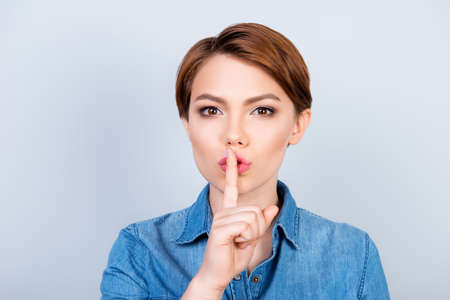 Shh! Girl is showing someone to keep quiet and to tell her secret on light blue background