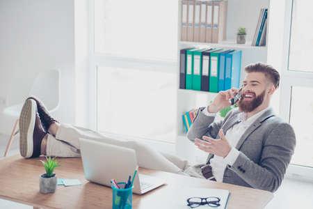 陽気な若い成功した男は、テーブルに足で職場に電話で話しています。彼はフォーマルな服装を着て、身振りで示すこと