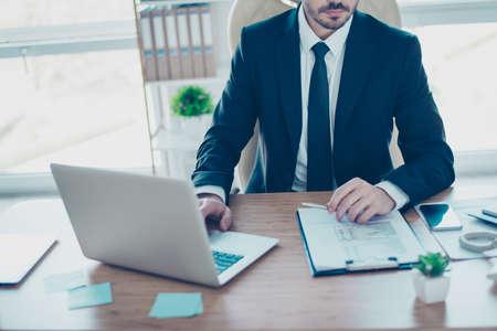 ノート パソコンと勉強の詳細レポートとテーブルに座ってネクタイを切り取られた写真の黒と白のフォーマルな服装で集中心実業家間近します。