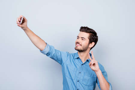 Handsome smiling young man is making selfie on smartphone and gesturing peace on light blue background Фото со стока