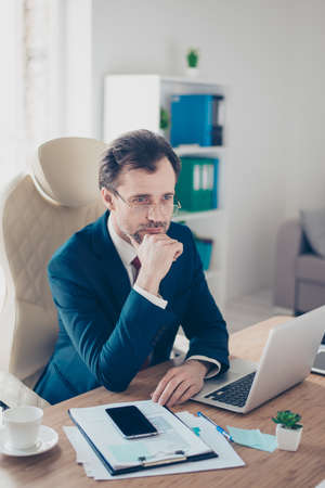 Serious businessman is concentrated on ideas of company development. He is wering formalwera, sitting at modern workstation