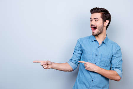 Portrait of young stylish guy in jeans shirt, pointing on copyspace. He is surprised and very excited
