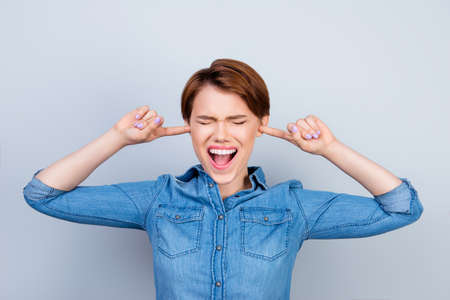 Young mad girl is screaming with closed eyes and ears. She doesn`t want to hear anyone