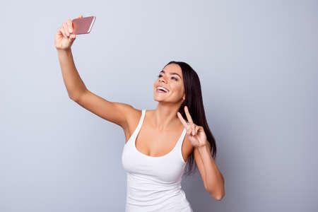 Ciérrese encima del retrato de la muchacha latina emocionada linda que hace el selfie con la cámara de su teléfono. Ella está en cierres casuales, tiene una sonrisa radiante y muestra un signo de la paz Foto de archivo