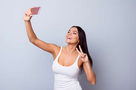 Sluit omhoog portret van leuk opgewekt Latijns meisje die selfie met camera van haar telefoon maken. Ze is in vrijetijdskleding gesloten, heeft een stralende glimlach en toont een vredesteken