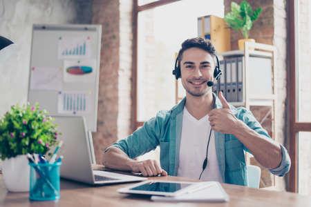 Lächelnder junger Betreiber des Kundenkontaktcenters sitzend am Tisch und Daumen-oben zeigend Standard-Bild - 81233493