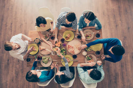 Top view of group of eight happy friends having nice food and drinks, enjoying the party and communication