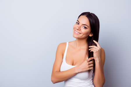Beautiful young latin american girl in casual clothes is touching her hair on light blue background