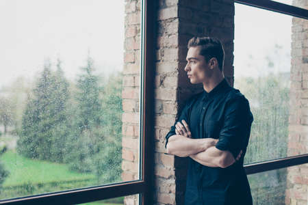 he: Young cute dreamy boy is looking far away in the window. He is in black outfit, his arms are crossed. He is serious and pensive Stock Photo