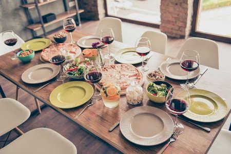 Laten we beginnen! Mooi gediende houten tafel met smakelijke gerechten en glazen wijn klaar voor het feest