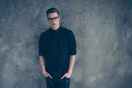 Portrait of young very handsome guy in black outfit and glasses looking straight in the camera, behind is grey background