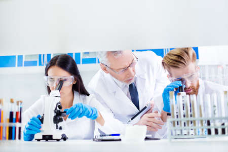 Teamwork concept. Professor is checking and controlling the group work of two lab interns. All three are focused on experiment and wearing labcoats