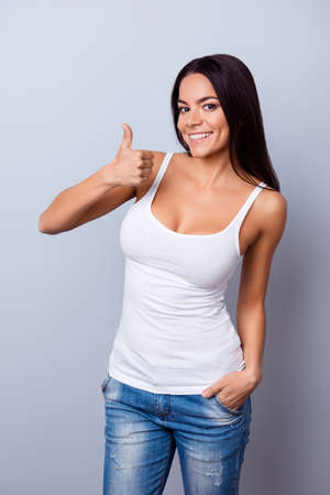 Cute hispanic girl is shwing like sign on light blue background in casual wear and with beaming smile
