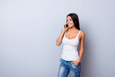 Cheerful young cute latin girl is talking on her phone and smiling. She is wearing casual clothes and put hand in the pocket