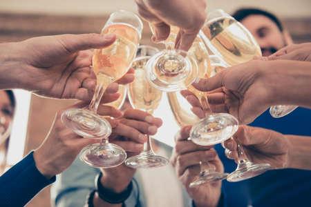 Geschoren onder het zicht van vrienden die de glazen bubbelende champagne vasthouden om samen een evenement te vieren Stockfoto
