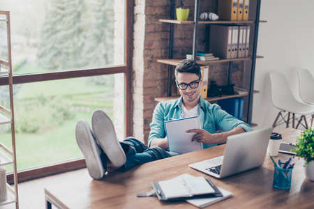 Portrait of smiling freelancer sitting at home in front of computer and writing action plan