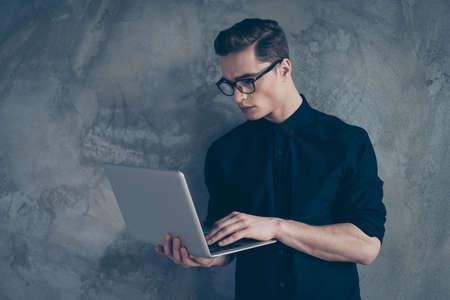 Vista lateral do jovem empresário atraente de camisa preta e óculos, usando seu laptop sobre o fundo cinza