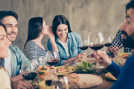 Sluit omhoog van twee meisjes die bij het feest roddelen. Vrienden vieren samen met drankjes en lekker eten Stockfoto