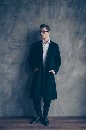 Young attractive businessman in glasses put his arms into pockets of black coat. He is standing near the grey wall