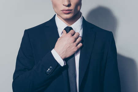 Close up cropped portrait of young handsome businessman in suit. He is fixing his tie. He stands on pure light background Stock Photo
