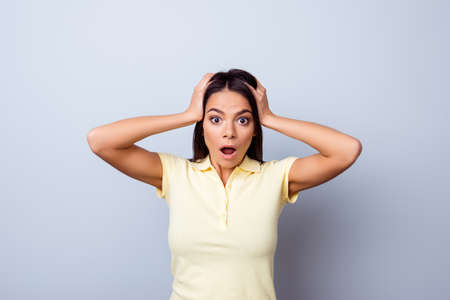 Omg! Close up portrait of amazed girl in casual wear on the light blue background