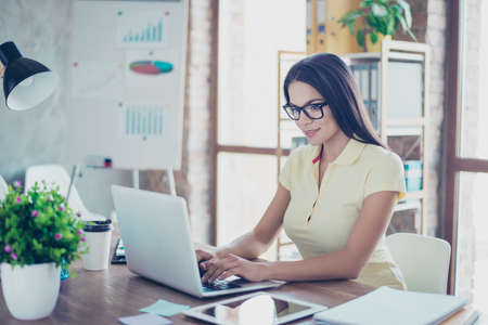 Portrait of beautiful smiling young businesswoman with glasses sitting at her workplace and typing on laptop