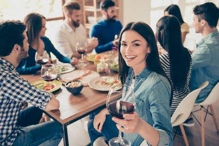 赤ワインのグラスを押しながら笑みを浮かべてカメラを見て女の子のクローズ アップ。彼女はポーズを覚えるためにカメラマンに党の瞬間