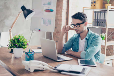 Jeune homme intelligent en jeans chemise et lunettes tenant un crayon à la main et en essayant de se concentrer sur le test Banque d'images