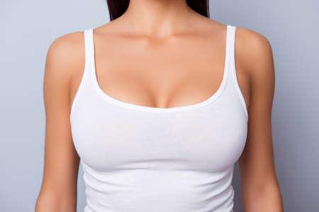 Cerca del pecho perfecto de la señora con la piel de bronce en camiseta blanca sobre fondo azul claro Foto de archivo