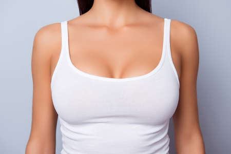 Close up of perfect lady`s chest with bronze skin in white singlet on light blue background