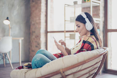 Portret van mooi gelukkig Latijns meisje zitten in stijlvolle leunstoel thuis met de telefoon en luisteren naar muziek met witte koptelefoon, bedekt met deken