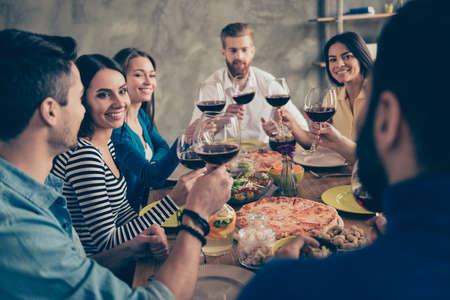 Prost! Freunde kamen am Tisch mit leckerem Essen mit Gläsern Rotwein zusammen, um einen besonderen Anlass zu feiern