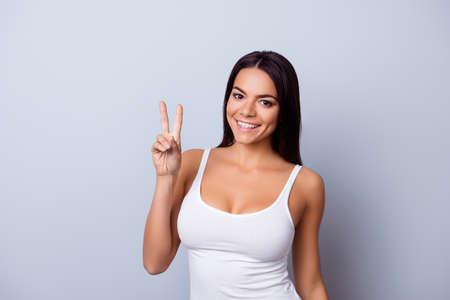 ¡Paz! Retrato de una joven latinoamericana juguetona. Ella está en una camiseta blanca casual de pie sobre el fondo azul claro puro
