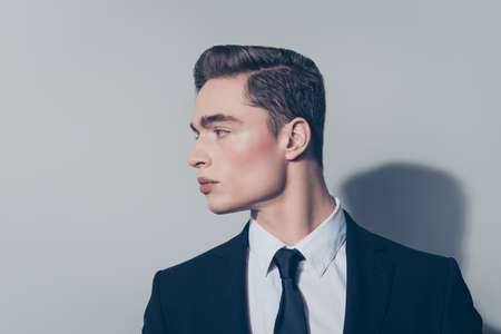 Close up of handsome mature guy with perfect hairstyle on pure light background. He is wearing suit and looking at his right Stock Photo