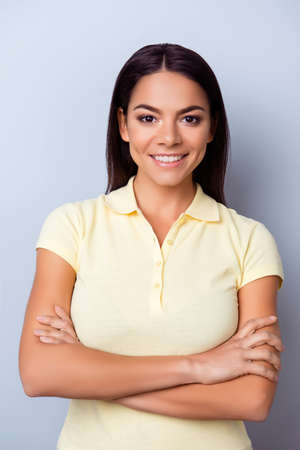 Young successful latino confident young woman standing with crossed hands on light background