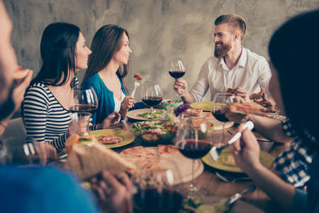 Young handsome bearded guy is telling the toast to a brunette cute girl, a birthday girl. Friends are celebrating with tasty dishes and drinks, smiling and enjoying themselves Stock Photo