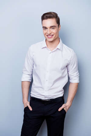 Perfection! Handsome young man in white shirt is standing on the pure light background. He looks confident and successful