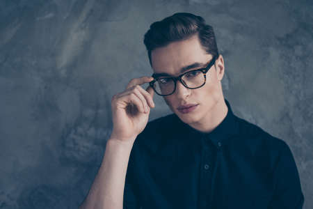 philosophic: Close up portrait of young very attractive guy in black outfit, wearing glasses and looking straihjt into camera on grey background Stock Photo